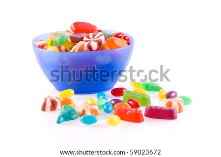Blue bowl with different kinds of colorful candy isolated on white. - stock photo