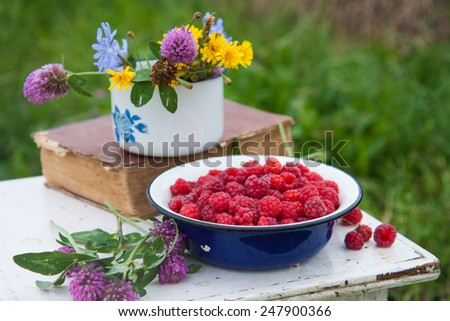 Blue bowl with raspberries, old book and cup with field flowers on the rustic white chair with the haymow on the background .  - stock photo
