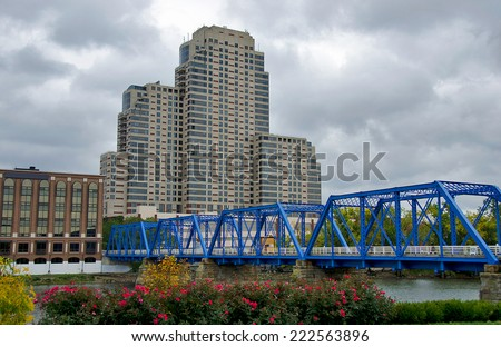 blue bridge in Grand Rapids Michigan with tall building on an overcast day - stock photo