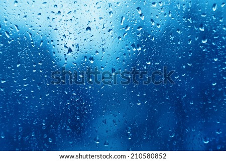 Blue bright texture of water drops on glass - stock photo