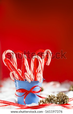 Blue bucket full of peppermint canes covered with snow. Christmas background with a room for text - stock photo