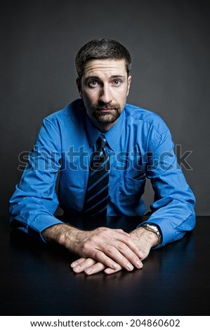 Blue businessman with folded hands