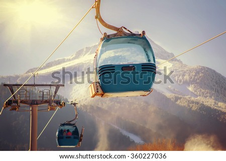 blue cable car lift at ski resort. vintage winter picture - stock photo