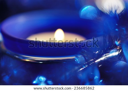 Blue candlestick on the blue draperies. Narrow depth of field. - stock photo