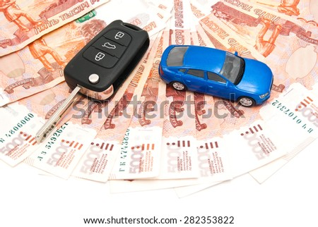 blue car, keys and banknotes closeup on white