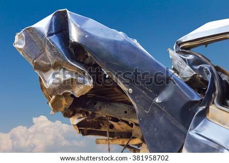 Blue car rear crumple collapse dents, damage due to collision with another vehicle collided with the sky as a backdrop. - stock photo