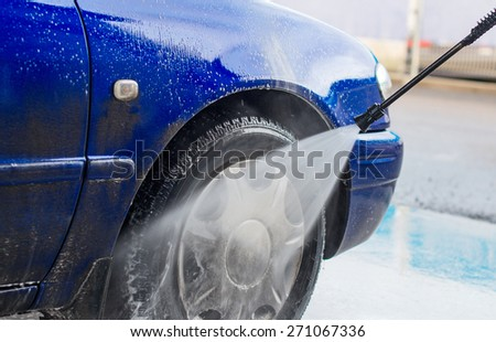 Blue car wash using high pressure water jet. - stock photo