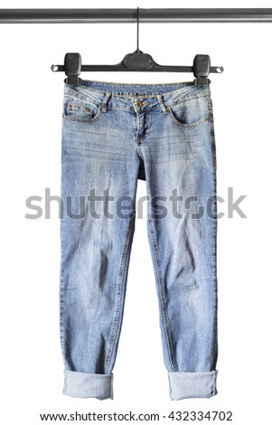 Blue casual jeans on clothes rack isolated over white - stock photo