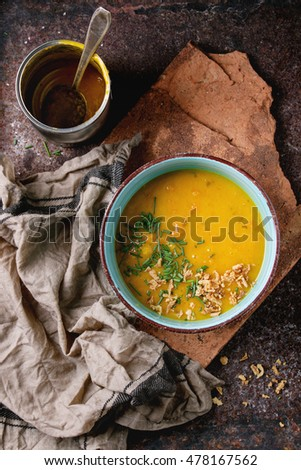 Blue ceramic bowl of carrot soup from can, served with onion chives, empty tin can and kitchen towel on clay board over old rusty iron background. Dark rustic style. Top view