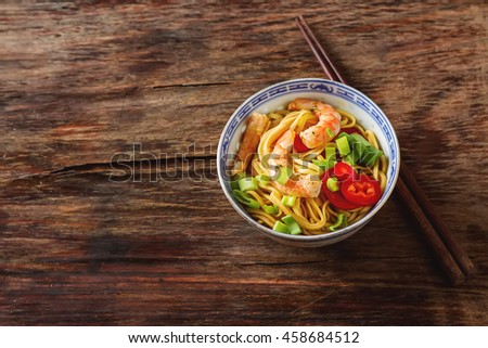 Blue ceramic cup noodles with vegetables, shrimps, green onions in sweet and sour Sauce with chopstikks on a dark wooden background. Selective focus.  - stock photo