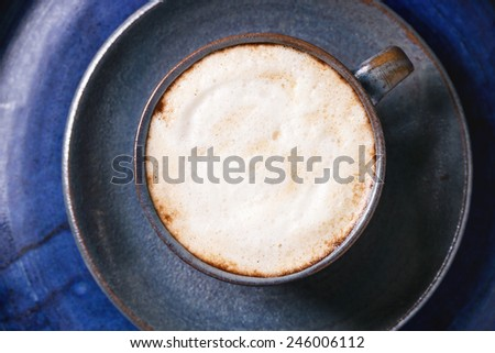 Blue ceramic cup of cappuccino over blue ceramic tray. Top view. - stock photo
