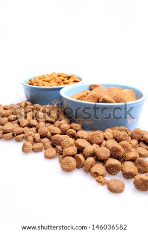 Blue ceramic dogs bowl. Dry dog food in bowl isolated on white background. Dry dog food isolated on white background - stock photo