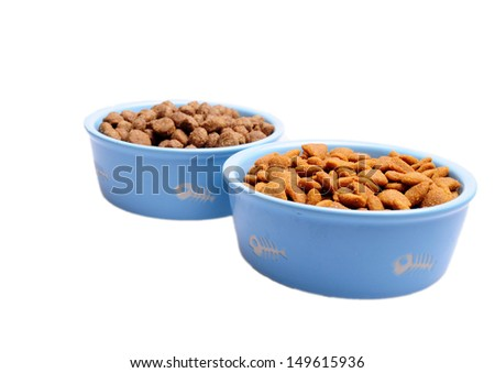 Blue ceramic dogs bowls. Dry dog food in bowl isolated on white background. Dry dog food isolated on white background