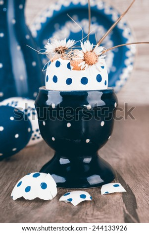 Blue ceramic Egg holder with flowers in egg shell and matching ceramics on wooden table. This image is toned - stock photo