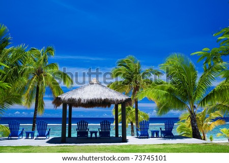 Blue chairs on a beach front on amazing beach