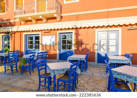 Blue chairs with tables in front of traditional Greek tavern in Fiskardo port, Kefalonia island, Greece - stock photo