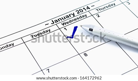 Blue check. Mark on the calendar at 1St January 2014 with pen, new year's day