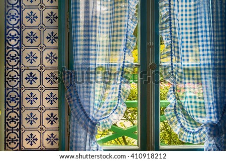Blue checkered curtains and blue tile in Monet's kitchen in Giverny, France - stock photo
