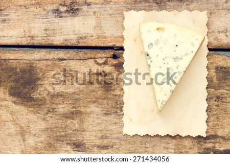 Blue cheese background with copy space. Piece of cheese with mold on wooden table - stock photo