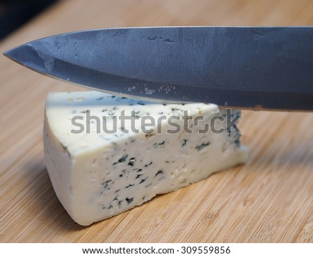 Blue cheese being cut with a knife.