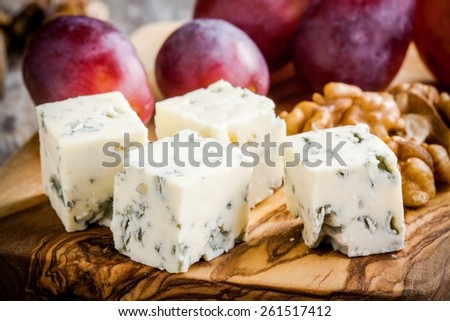 Blue cheese close-up with grape and nuts on a wooden cutting board - stock photo