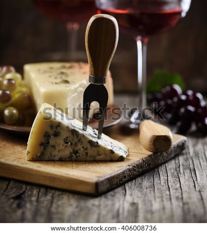 Blue cheese slice and red wine on wooden table. - stock photo