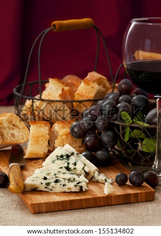 Blue cheese with a glass of red wine - stock photo