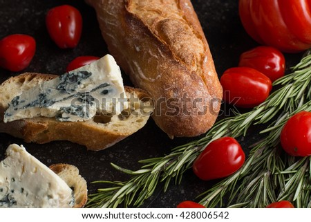 Blue cheese with french baguette, tomato and herbs on black marble table. Traditional snacks in France and Italy. - stock photo