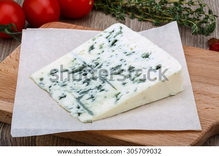 Blue cheese with herbs and spices on the wood background - stock photo