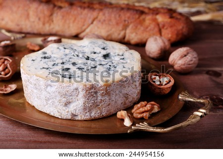 Blue cheese with nuts, baguette and hay on metal tray and wooden table background - stock photo
