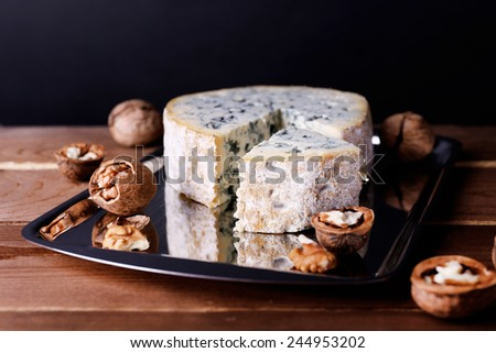 Blue cheese with nuts on metal tray and wooden table and dark background - stock photo