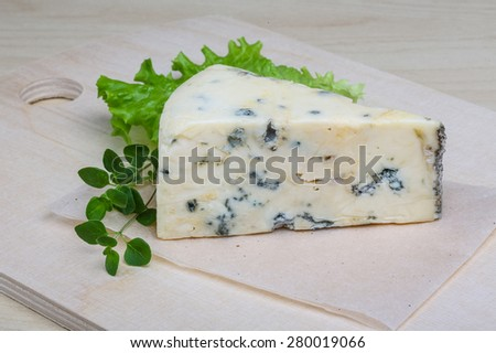 Blue cheese with oregano and salad leaves - stock photo