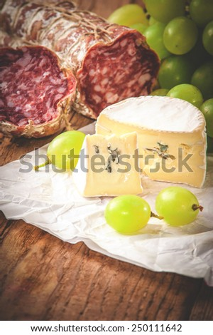 Blue cheese with salami on a wooden rustic table - stock photo