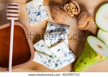 Blue cheese with slices of pear, nuts and honey on bamboo wooden cutting board. Flat lay.