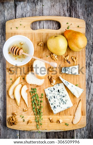 Blue cheese with slices of pear, nuts and honey on wooden cutting board top view