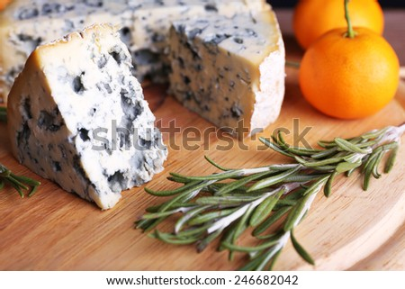 Blue cheese with sprigs of rosemary and oranges on board and wooden table background - stock photo