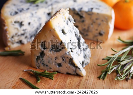 Blue cheese with sprigs of rosemary and oranges on wooden board background - stock photo