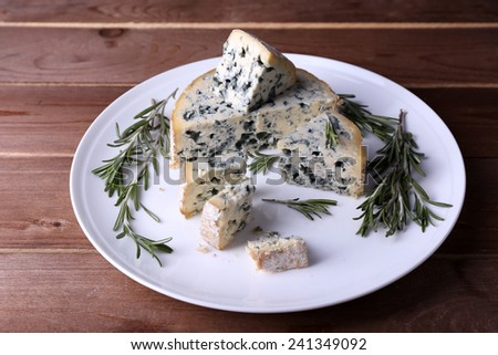 Blue cheese with sprigs of rosemary on plate and wooden table background - stock photo