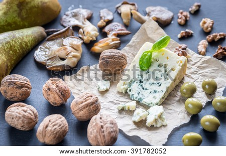 Blue cheese with walnuts, oyster mushrooms and green olives - stock photo