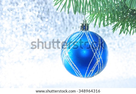 Blue Christmas ball and green tree on shiny background with copy space for text. Christmas background or greeting card. Selective focus. - stock photo