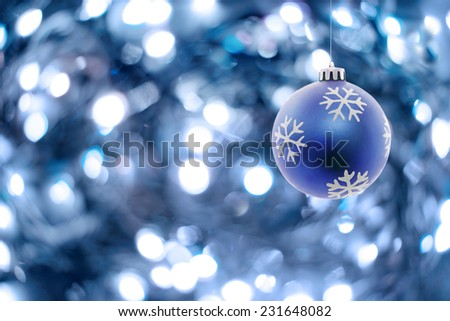 Blue Christmas ball hanging and blue lights in the background.Copy space on the left side - stock photo