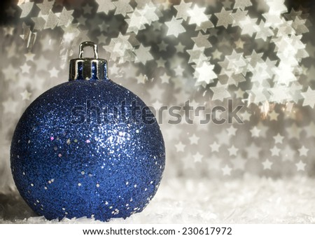 Blue Christmas ball in the snow on a beautiful bokeh background.