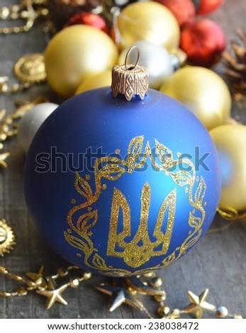 Blue Christmas ball with Ukrainian emblem, Christmas decorations, holiday, wooden background - stock photo
