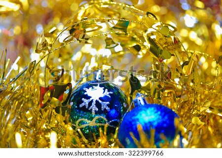 Blue christmas balls in the golden tinsel defocused backgrounds - stock photo