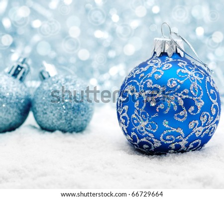 Blue christmas balls on the snow over blurry background, shallow depth of field - stock photo