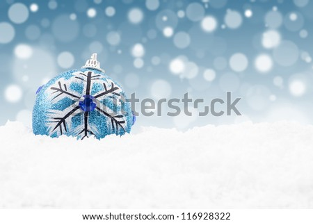 Blue christmas bauble on the snow with christmas lights background - stock photo