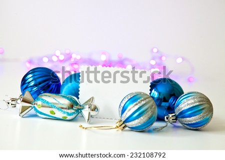 Blue Christmas toys, white paper card for your text