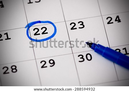 Blue circle. Mark on the calendar at 22. - stock photo