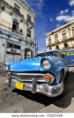 Blue classic american car in havana street with eroded buildings in the background - stock photo