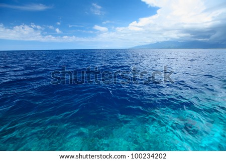 Blue clear sea with waves and sky with clouds - stock photo